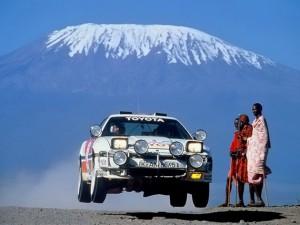 Lars-erik torph i Monte carlo, rallybil i luften, kebnekaise i bakgrunden och två afrikanska kvinnor som står och tittar.